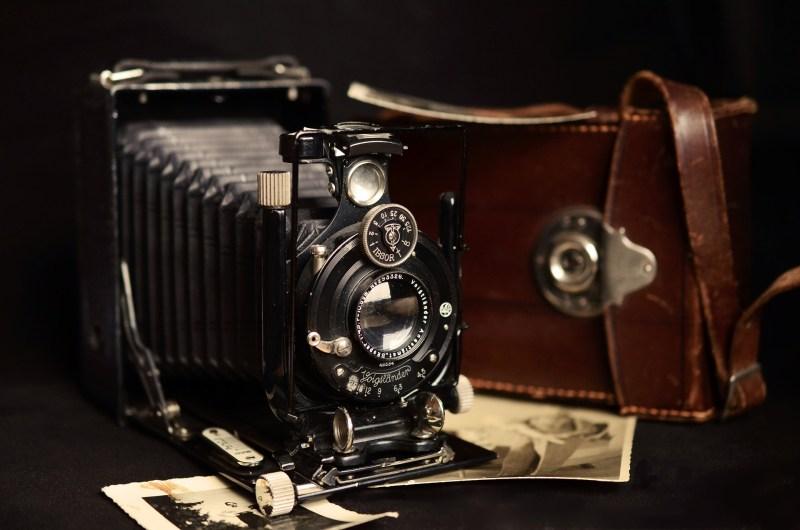 Cámara fotográfica antigua con funda de piel y varias fotografías en sepia