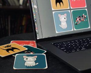 Macbook with coasters designed in Adobe Illustrator