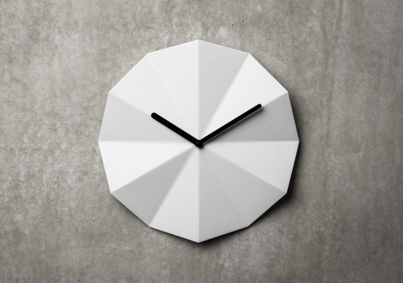 Delta white composite clock by LAWA Designs hung on a cement wall