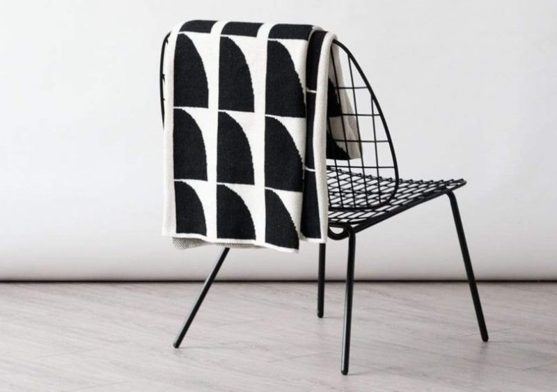 Jaws Black and White Throw by Happy Habitat slung over a chair