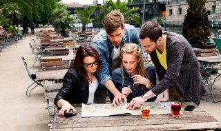 Four Young Adults with Map at Cafe