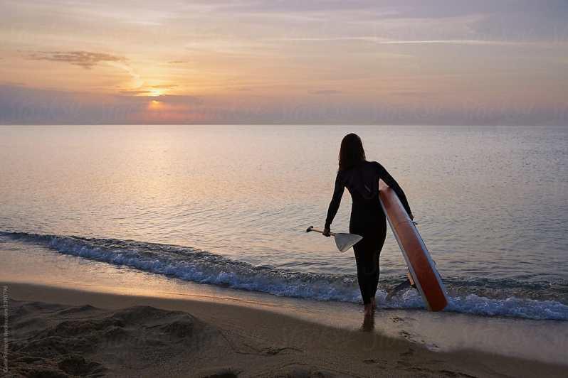 Žena jdoucí po okraji pláže za soumraku v neoprénu s paddleboardem a pádlem.