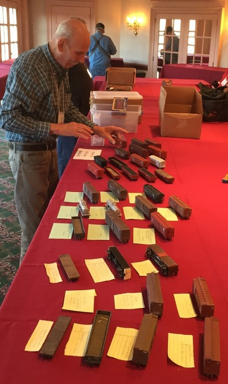 Bill Hanley sets out a number of HO scale freight cars for display in the model room.