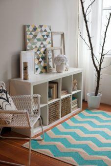 Sala de estar com tapete em chevron fazendo par com quadro de estampa geométrica
