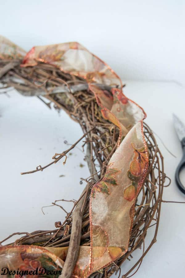 adding decorative ribbon to a wreath