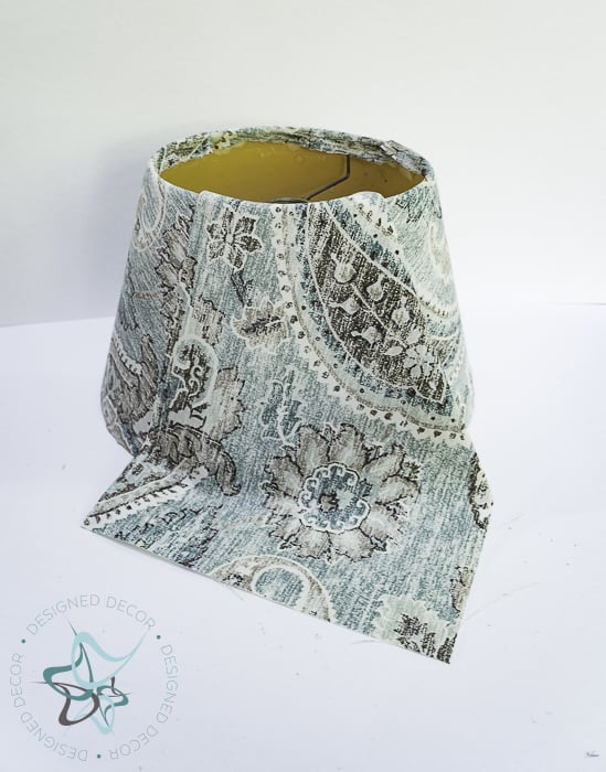 once fabric is dry, trim extra fabric around edges of lampshade