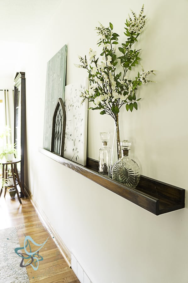 Picture of wall picture ledge, decorated with artwork and home decor items
