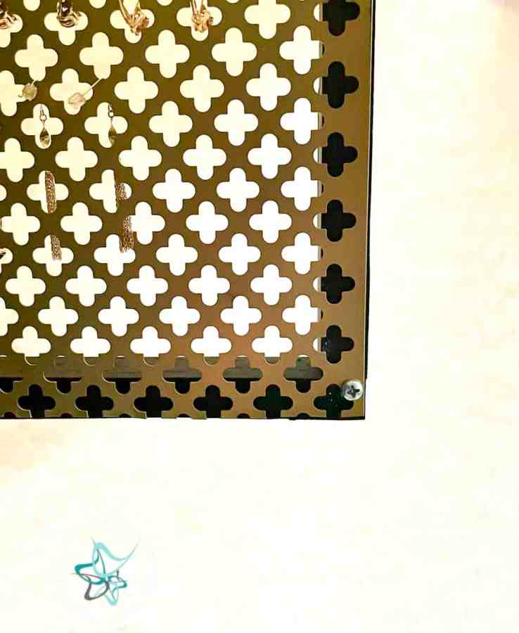 gold decorative metal sheet screwed into a wood frame