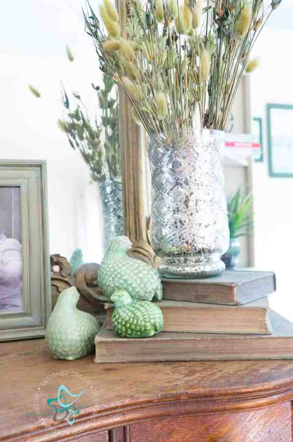 entryway table with ceramic birds on books and a vase of dried flowers