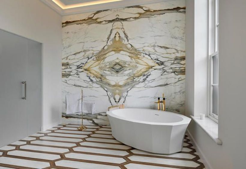 bath with white free standing tub and back wall of marble