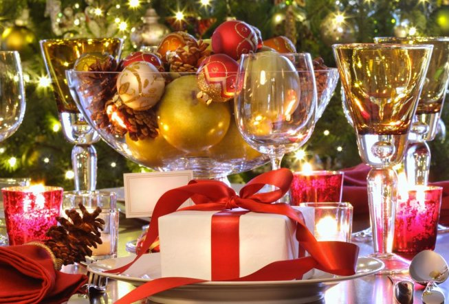 wine glasses, christmas ornaments in bowl, pine cone, wrapped present with red ribbon