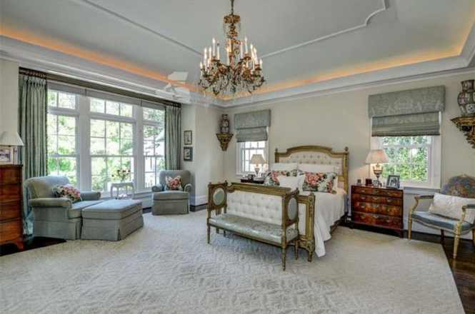 French Provincial Bedroom With Tufted Bed Chandelier Lounge Chair Tray Ceiling And Vintage