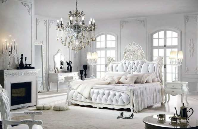 Bedroom With European Style Tufted Bed Fireplace Chandelier And White French Provincial Furniture