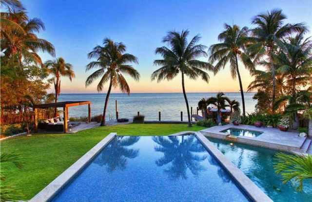 Okyanus manzaralı ve palmiye ağaçlı sonsuzluk havuzu