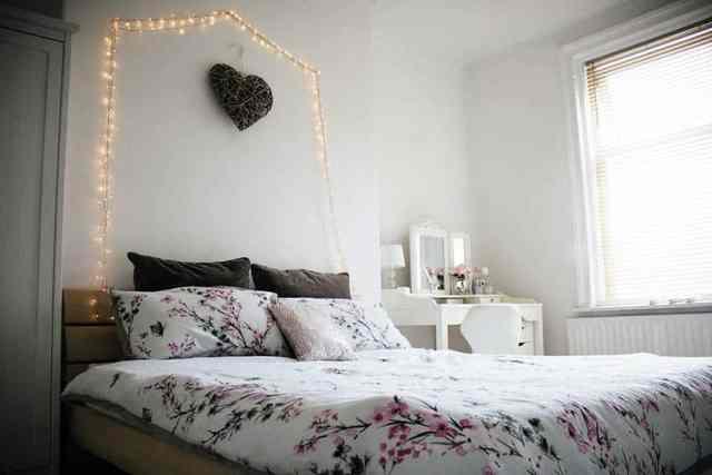 Yatağın üstünde duvara asılı ışıklar ile genç kız yatak odası