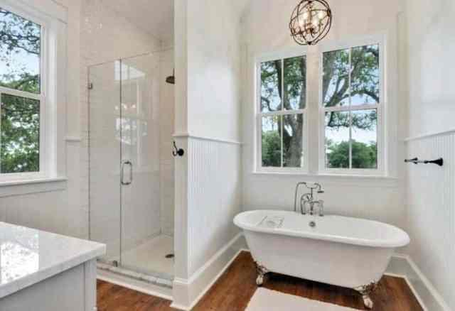 Ahşap zemin, duşakabin ve ayaklı küvet içeren geleneksel banyo