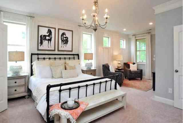 Bej halı avizeli ve oturma alanlı yatak odası