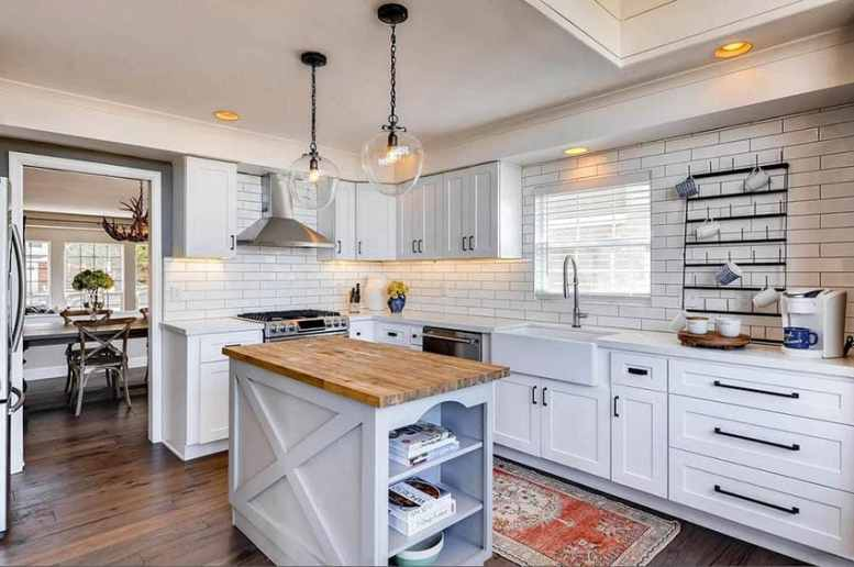 Cottage kitchen with island and open shelving cookbook storage