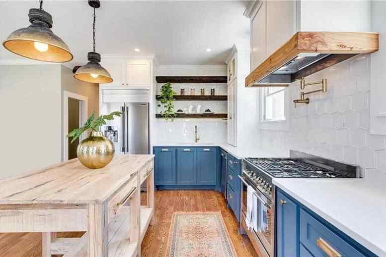 Boerderij keuken met blauwe kasten wit kwarts tegen open rekken en houten eiland