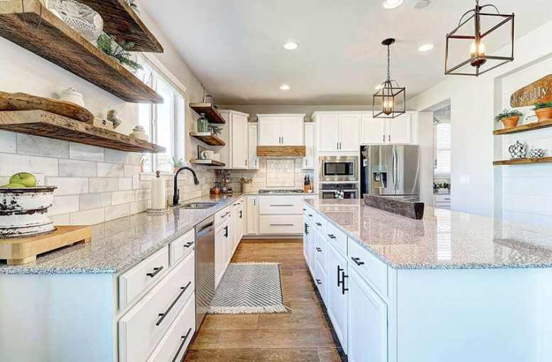 Kitchen with white cabinets and reclaimed wood open shelving with decor pieces