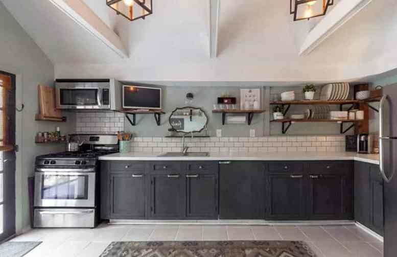 L shaped kitchen with dark lower cabinets and open shelving