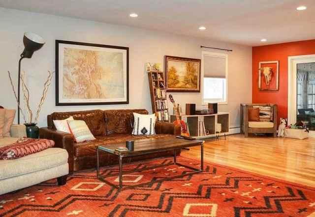 Kahverengi kanepe turuncu vurgulu duvar turuncu halı ile oturma odası