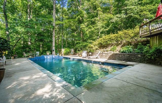 Eğimli tepe ve beton veranda üzerinde istinat duvarları olan arka bahçe havuzu