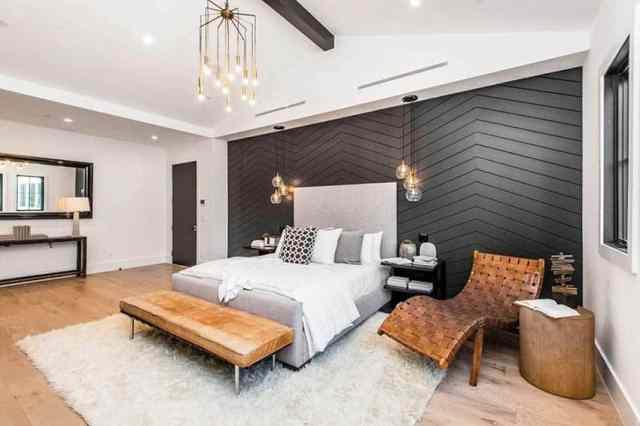 Ahşap zemin ve kirişli, siyah vurgulu duvar ve kolye ışıklı modern çiftlik evi yatak odası tasarımı