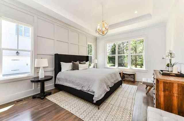 Tepsi tavan küre avize ve panelli duvar ile modern çiftlik evi ana yatak odası