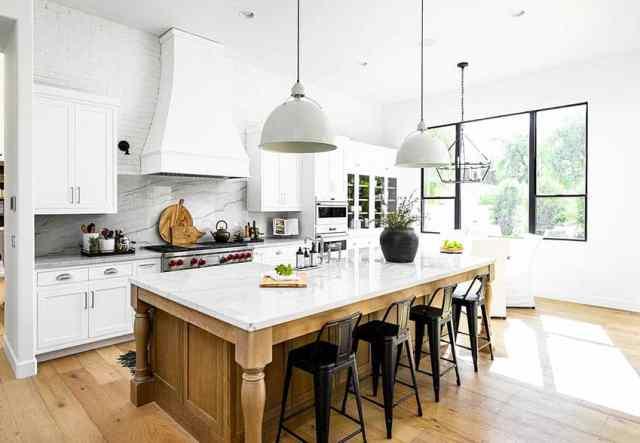 Mermer ve kuvars tezgahlar, beyaz dolaplar, sarkıt ışıklar ve backsplash ile şef mutfağı