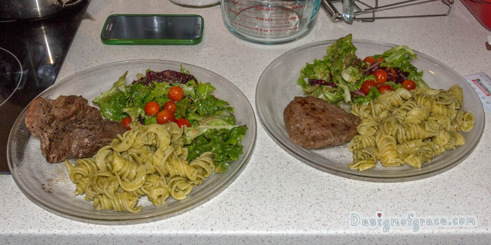 2 plate of food with the kangaroo steak on the left and the patty on the right with pesto pasta and salad.