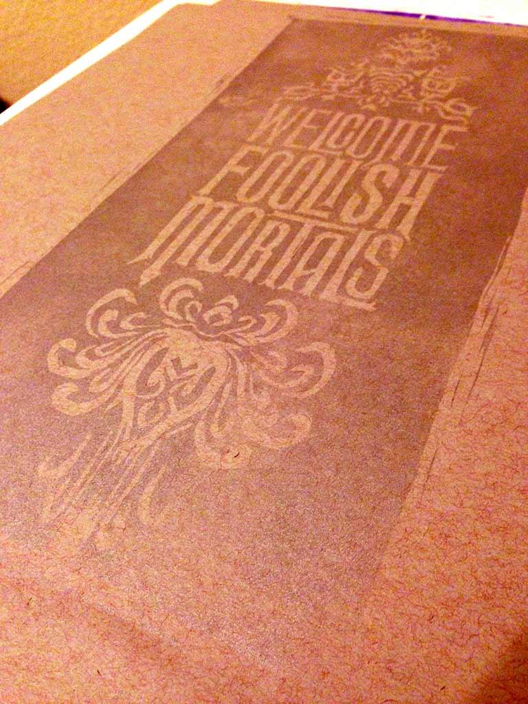 "linoleum block print of ""welcome foolish mortals"""