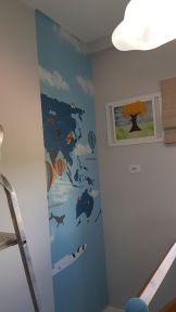 papel de parede mapa mundi Infantil lamina sendo aplicada para ajustes