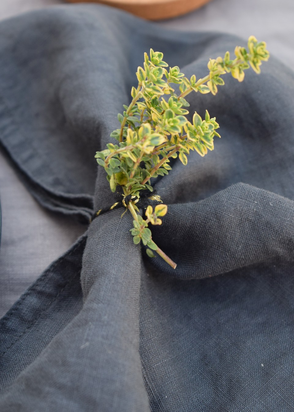 simple relaxed outdoor tablescape ideas, scandinavian linen botanical, simple lemon thyme sprig crumpled linen