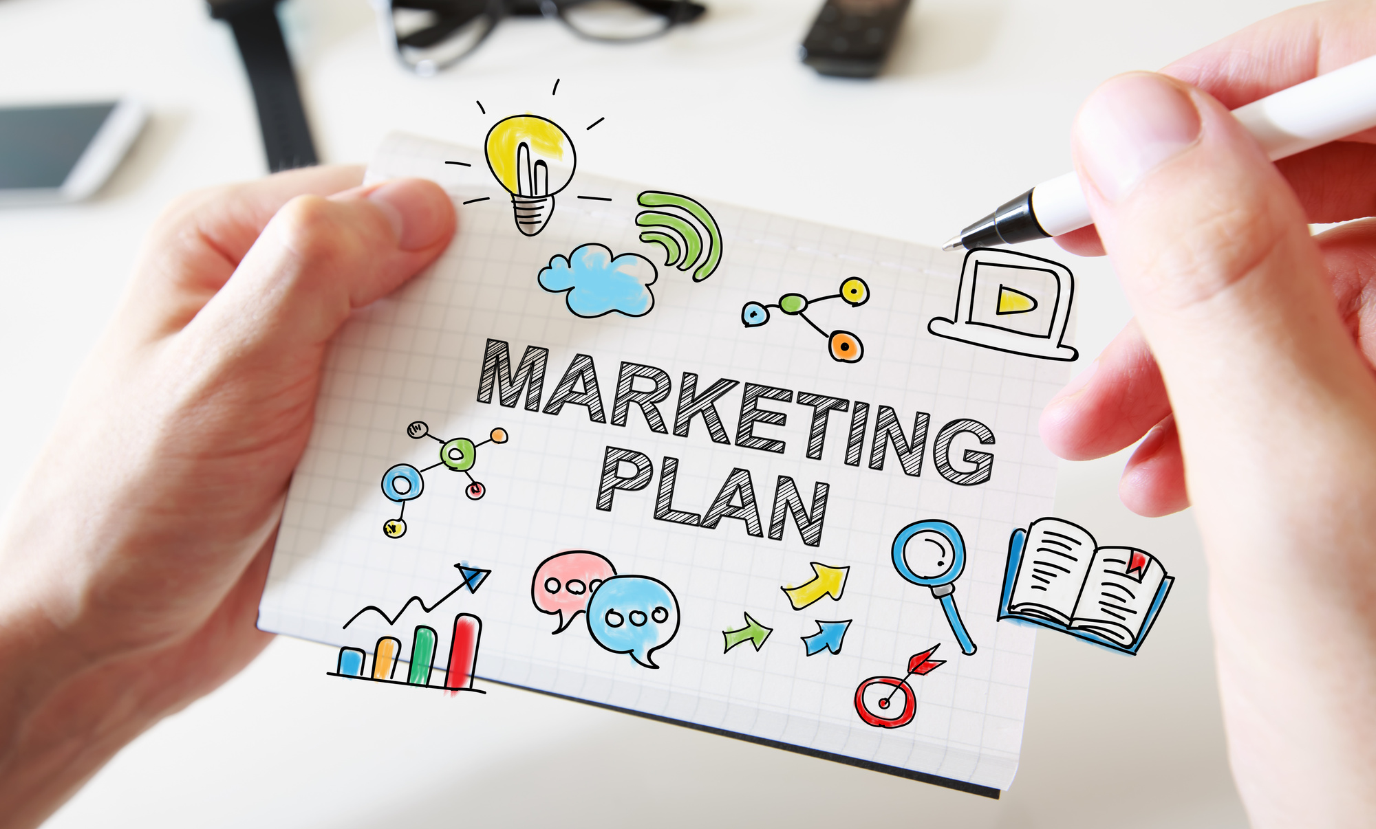 Mans hand drawing Marketing Plan concept on notebook