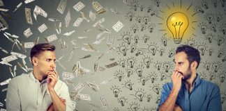 two serious businessmen looking at each other one under money rain another with bright ideas