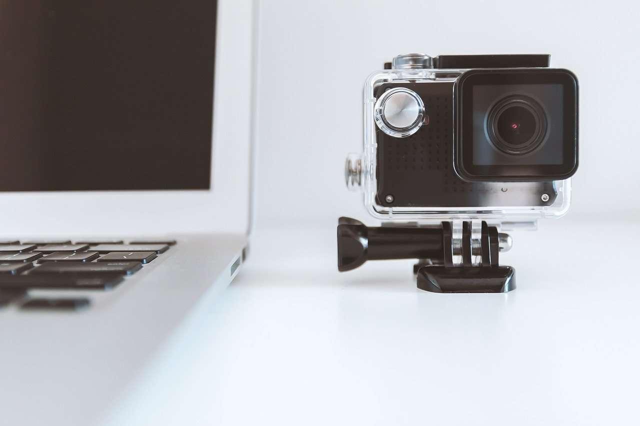 A camera next to a laptop