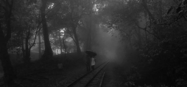 couple with umbrella on train tracks Matheran