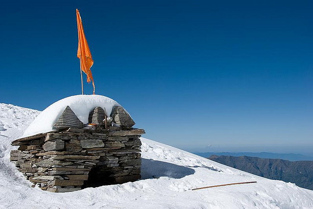 saffron flag on top of temple surrounded by snow in roopkund