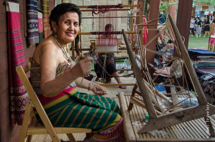 Making Thai fabric using hand loom and spinning wheel
