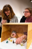 """Rachel Kalman (left) and Sara Weininger interact with the exhibit titled """"Freedom of Assembly"""" by Cole Pruitt and Lara Head at the Parabola: Assembly exhibition, Des Lee Gallery, Washington University, St. Louis, MO"""