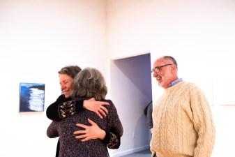 Melissa Miller hugs Karen Goellner (facing away) with Bob Merz at the Robert C. Smith Retrospective Exhibit Opening, Des Lee Gallery, St. Louis, MO