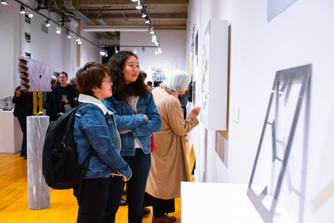 """Danning Liang (l) and Suyin Yao view work at the Opening reception of the """"Decoys and Depictions: Images of the Digital"""" Exhibition at the Des Lee Gallery, Washington University, St. Louis, MO"""