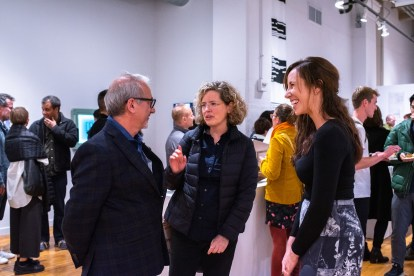 """Carmon Colangelo (l), Dean of the Sam Fox School of Design & Visual Arts, talks with Heather Woofter, Director of the College of Architecture, and Constance Vale (r), Assistant Prof., at the Opening Reception of the """"Decoys and Depictions: Images of the Digital"""" Exhibition at the Des Lee Gallery, Washington University, St. Louis, MO"""