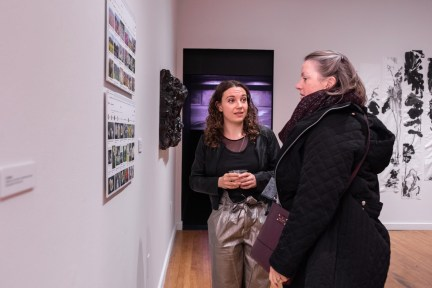 """Sarah Knight (c) talks with Beverly Knight while they view """"Fukushima Flowers"""" by Takura Suzuki on display at the Parabola: Extraterrestrial Exhibit, Des Lee Gallery, Washington University, St. Louis, MO"""
