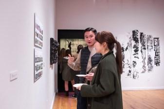 "Takura Suzuki (l) talks about his piece ""Fukushima Flowers"" with Yeeun Kang at the Parabola: Extraterrestrial Exhibit, Des Lee Gallery, Washington University, St. Louis, MO"