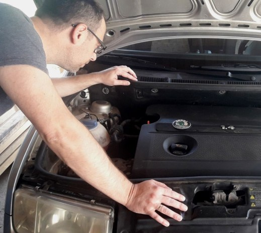 man-making-inspection-under-hood