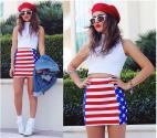 Falda tipo tubo con la bandera de Estados Unidos, combinada con una polera blanca, zapatillas blancas, una boina roja y labios rojos.