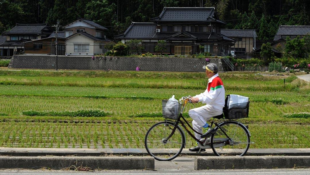 Japonais se déplacant à vélo sur un chemin de campagne à Noto