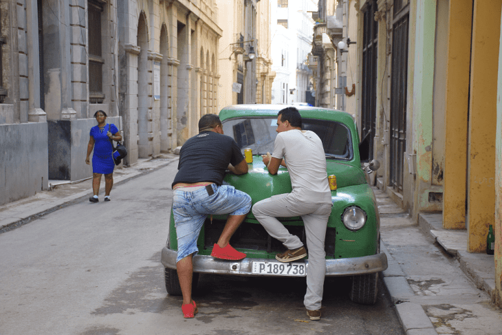 Two Cubans share a beer in the street on a vintage car
